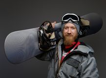 Confident man with a red beard wearing a full equipment holding a snowboard on his shoulder, smiling and looking at a. Camera stock image