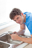 Confident man repairing his sink in the kitchen Stock Images