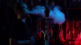 A young man smokes a hookah in a hookah bar on the dark background, slow motion. Confident man resting in lounge restaurant on against black background, smoking stock footage