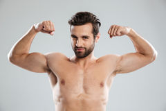 Confident man showing his biceps and looking at camera Stock Images