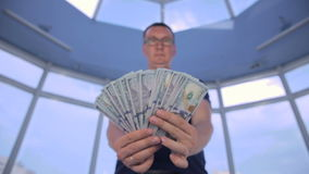 Confident man showing money, US dollars into camera. HD stock video