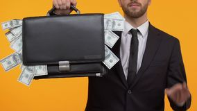 Confident man showing ok sign and full case of money, stable high wages at work. Stock footage stock video footage
