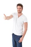 Confident man showing thumb up smiling Royalty Free Stock Photography