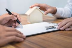 Confident man signing contract of loan agreement document with b. Roker agent, Real Estate concept Stock Photo