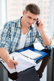 Confident man sitting with bills and talking on cell phone Royalty Free Stock Photography