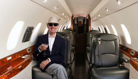 Confident man sitting at his seat in private airplane and smiling Stock Photos