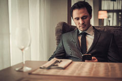 Confident man with smart phone in restaurant. Royalty Free Stock Photo