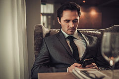 Confident man with smart phone in restaurant. Stock Photos