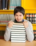 Confident Man With Stacked Books Sitting In. Portrait of confident young man with stacked books sitting against bookshelf in university library Stock Photos