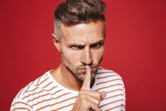 Confident man in striped t-shirt holding index finger on lips wi. Th strict look isolated over red background royalty free stock photography