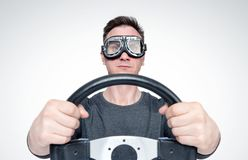 Confident man in stylish goggles with steering wheel, car driver concept stock photography
