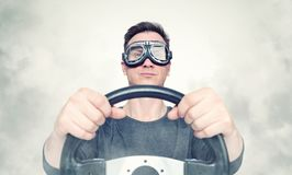 Confident man in stylish goggles with steering wheel, smoke around. Front view. Car driver concept stock photos