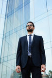 Confident man in a stylish suit stands near a high modern office building Royalty Free Stock Photography