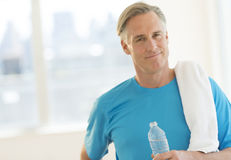 Confident Man With Towel And Water Bottle At Club. Portrait of confident mature man with towel and water bottle at health club royalty free stock image
