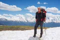 Confident man traveler with big backpack on the mountain trail Stock Photo