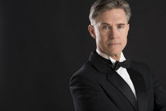 Confident Man In Tuxedo Staring Against Black Background stock images