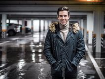 Confident man in underground car parking. Young trendy man in winter outerwear standing in car parking and smiling to the camera Royalty Free Stock Images