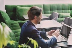 Confident man using gadgets in restaurant Stock Photo