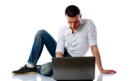 Confident man using laptop on the floor Royalty Free Stock Photography