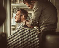 Confident man visiting hairstylist in barber shop. Stock Photo