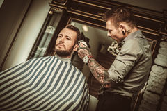 Confident man visiting hairstylist in barber shop. Royalty Free Stock Photos