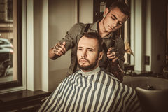 Confident man visiting hairstylist in barber shop. Stock Image