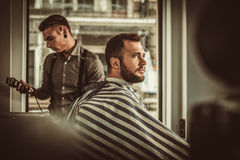 Confident man visiting hairstylist in barber shop. Royalty Free Stock Images