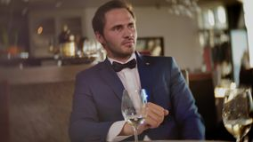 Confident man waiting for somebody in restaurant stock video footage