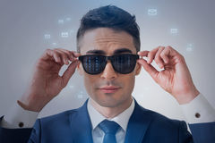Confident man is wearing futuristic goggles. Communications concept. Portrait of pleasant elegant young businessman is touching his sunglasses with reflection of Royalty Free Stock Photography