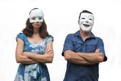 Confident man wearing a happy face mask standing beside a unconfident woman who wearing a sad face mask royalty free stock photography