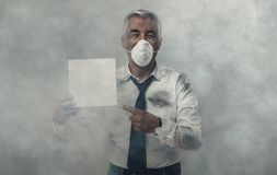 Man with pollution mask holding a sign. Confident man wearing a pollution mask and holding a blank sign, he is surrounded by smog stock photography