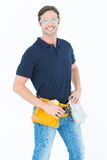 Confident man wearing tool belt over white background Stock Image