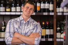 Confident man at wine selection. Portrait of confident male holding hands folded with a selection of wines in the background Royalty Free Stock Photos