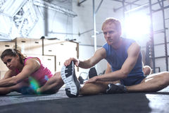 Confident man and woman doing stretching exercise in crossfit gym royalty free stock image