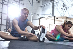 Confident man and woman doing stretching exercise in crossfit gym