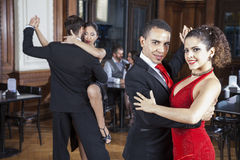 Confident Man And Woman Performing Tango In Restaurant Stock Images