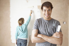 Confident Man With Woman Using Paint Roller Stock Images