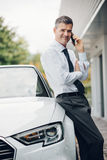 Confident manager leaning on his car. Confident smiling manager having a business call with his smartphone and leaning on his expensive car outdoors Stock Image