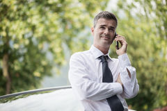 Confident manager leaning on his car. Confident smiling manager having a business call with his smartphone and leaning on his expensive car outdoors Stock Photography