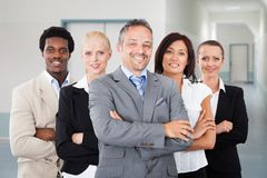 Confident manager standing arms crossed with team stock photography