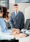 Confident Manager Standing In Front Of Customer. Portrait of confident manager standing in front of customer service representatives in office Royalty Free Stock Photography