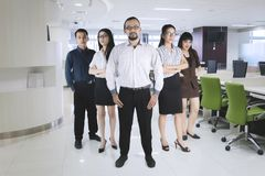 Confident manager standing with his team at office. Full length of a confident male manager looking at the camera while standing with his team in the office Royalty Free Stock Photo