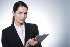 Confident manageress working on a tablet Royalty Free Stock Image