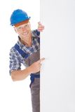 Confident manual worker holding billboard. Full length portrait of confident young manual worker holding billboard over white background royalty free stock image