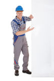 Confident Manual Worker Holding Billboard. Full length portrait of confident young manual worker holding billboard over white background royalty free stock photos