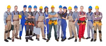 Confident manual workers against white background. Panoramic shot of confident manual workers standing against white background Royalty Free Stock Images