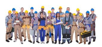 Confident manual workers against white background. Panoramic shot of confident manual workers standing against white background Stock Images