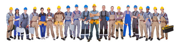 Confident Manual Workers Against White Background. Panoramic shot of confident manual workers standing against white background Royalty Free Stock Photos