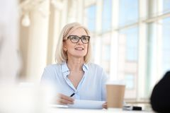 Confident mature business woman leader coach speaking at meeting. Negotiations, old middle aged female manager executive mentor talking participating in stock image