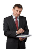 Confident mature businessman holding a marker and writing in a n stock images